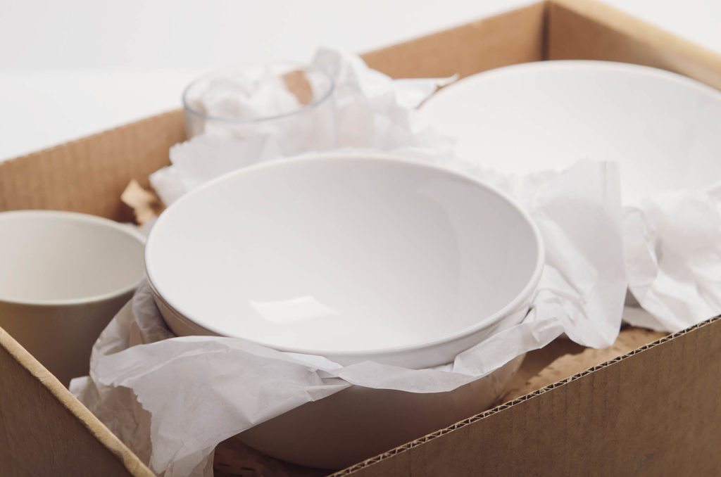 Clean white dishes in paper packed in cardboard box. Concept relocation.